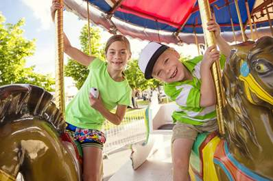 Kids having fun riding on a carnival carousel.