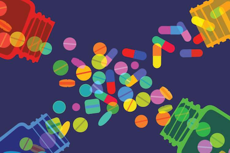 Pills spilling out of four bottles, digital image.