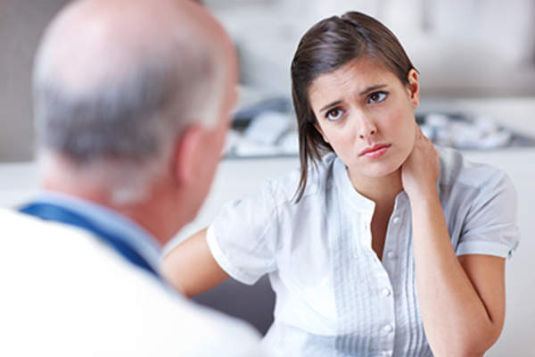 Woman with rheumatoid arthritis pain talking to her doctor.