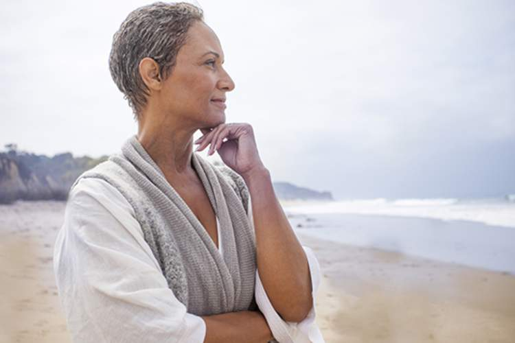 Senior woman contemplating on the beach.