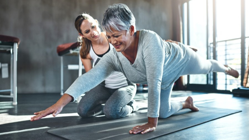 Younger woman helping senior woman at gym