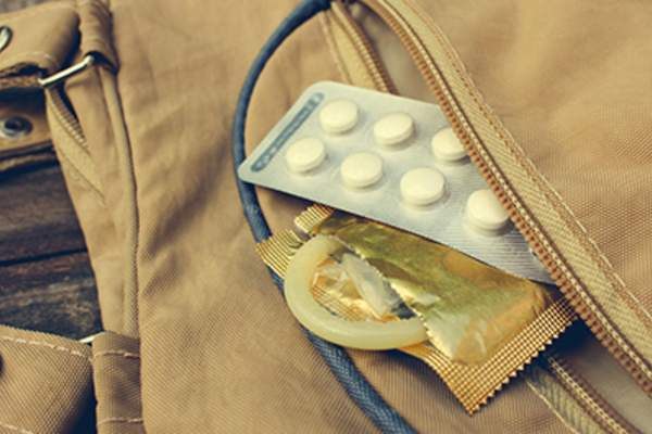 Birth control pill and condom peeking out from pocket.
