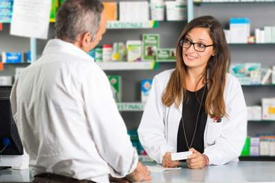 Older man at pharmacy counter talking to pharmacist image.