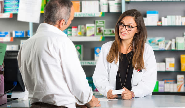 Man at pharmacy counter talking to pharmacist image.