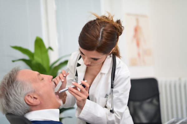 Doctor examining patient that is having difficulty swallowing.