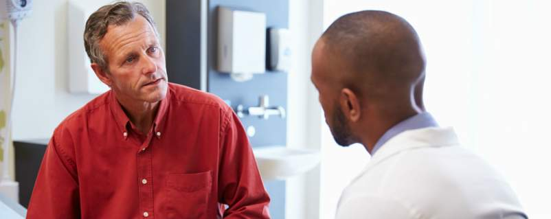 Man Talking with doctor in doctors office