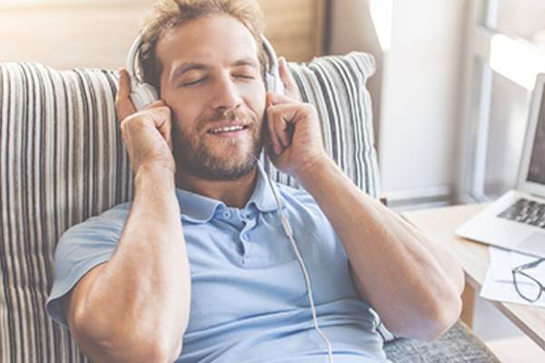 Man relaxing and listening through headphones.