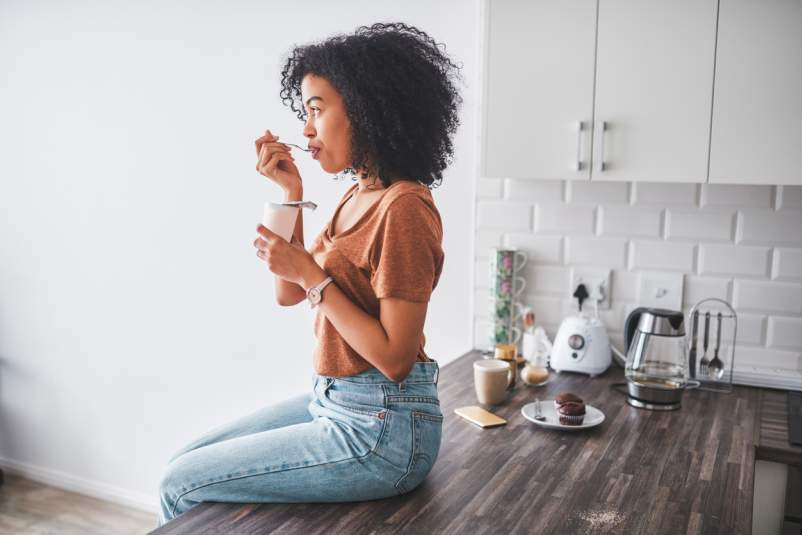 Young woman sitting on kitchen counter eating yogurt.