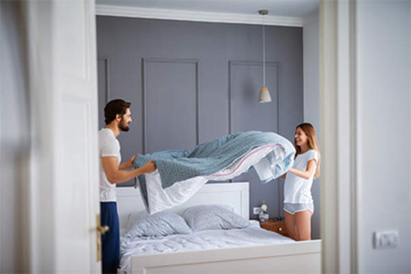 Young couple making the bed.