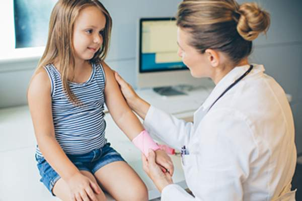 Child having her wrist wrapped by a doctor.