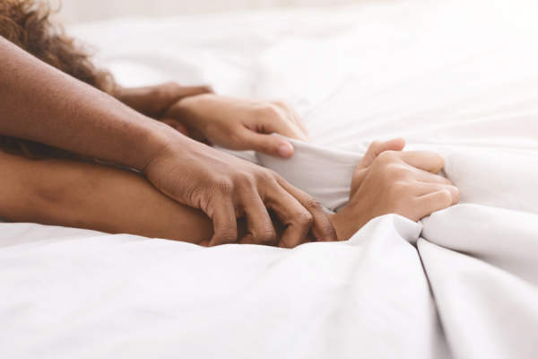 couple in bed, close up of hands