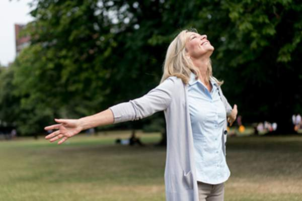 Woman outside with arms open wide.