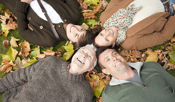Family lying in autumn leaves in a park.