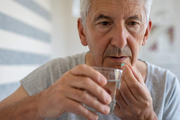 Senior man swallowing an oral agent for prostate cancer treatment.