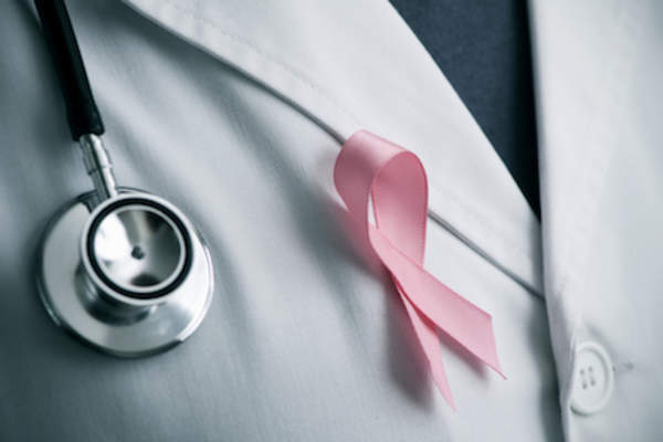 Pink breast cancer awareness ribbon on doctors white coat.
