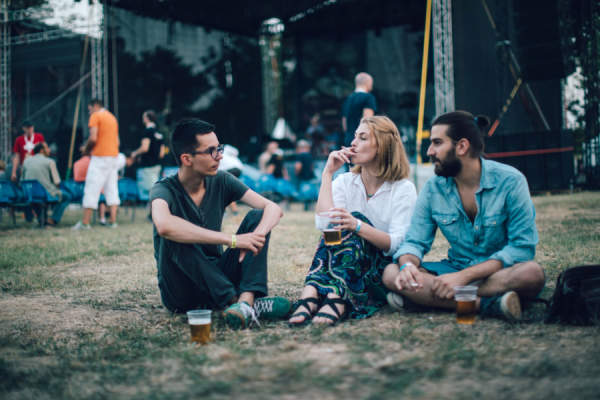 three friends at music festival, two are smoking cigarettes