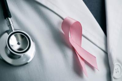 Pink breast cancer awareness ribbon on doctors lab coat.