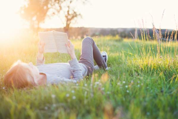 Girl laying on her back in a field reading.