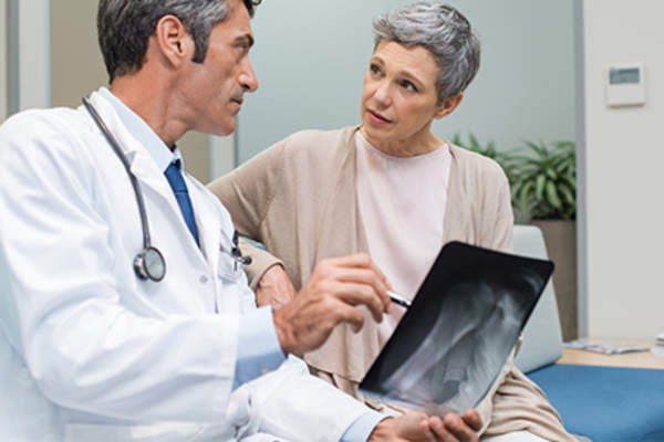 Woman with osteoporosis talking to doctor holding x-ray.