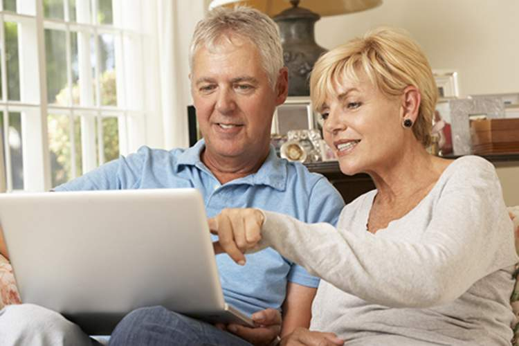 Mature couple looking up cancer resources on a laptop.