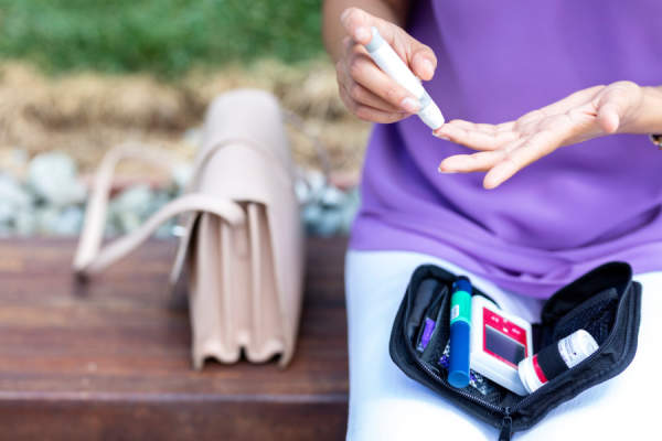 woman using insulin outside with carrying case