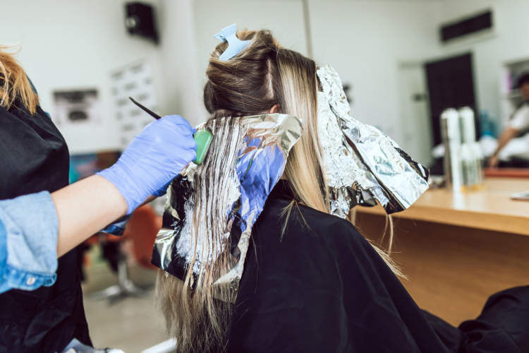 Young woman getting her hair dyed and highlighted.