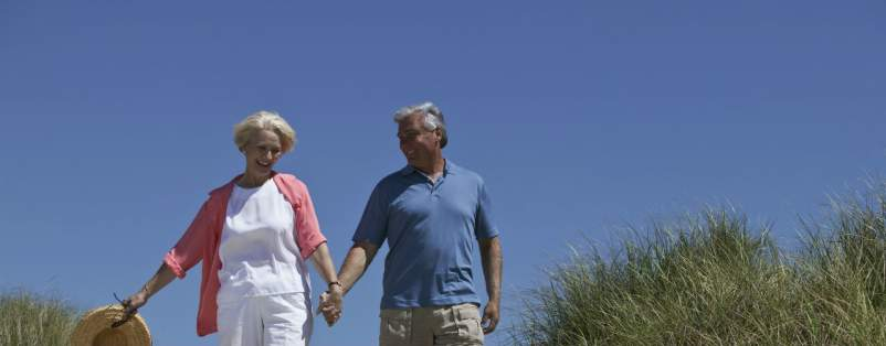 older couple holding hands walking on boardwalk