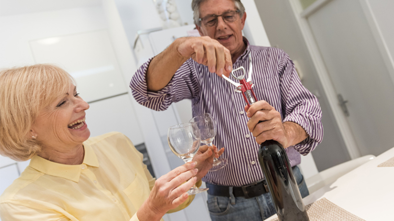 Senior couple opening a bottle of wine in the kitchen at home.