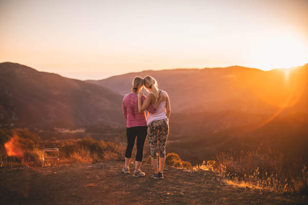 mother and daughter hugging on hill at sunset after hike