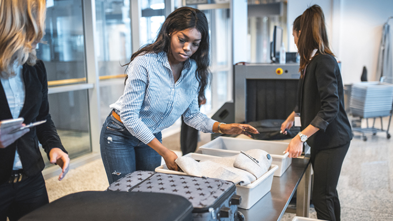Woman going through luggage check at airport security.