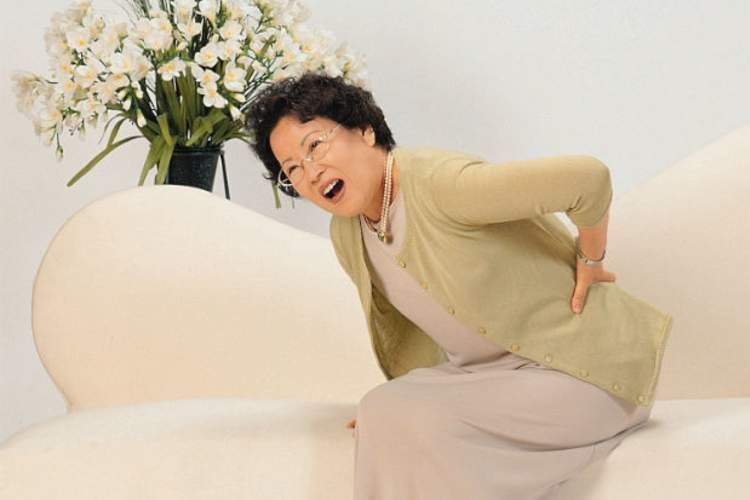 A woman having a back spasm grabs her back in pain.