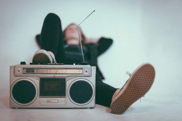 Person lying down with a radio while listening to music