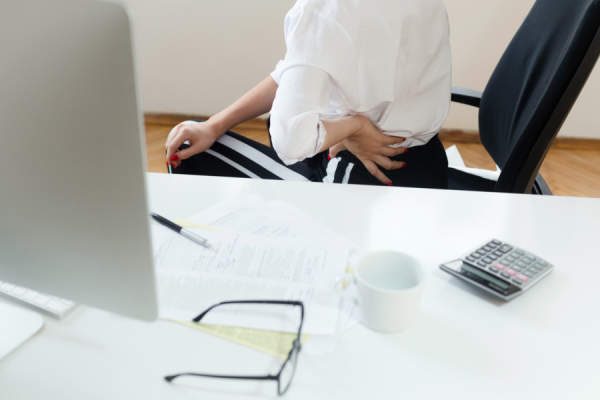 Businesswoman at desk suffering from backache