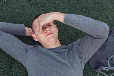 Man lying down on the ground after exercise.