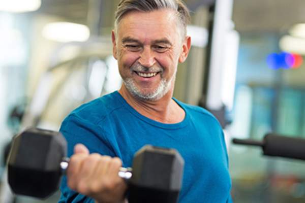 Senior man lifting a dumbbell at the gym.
