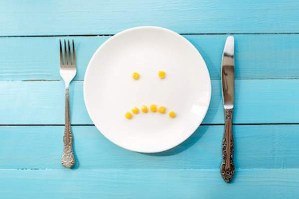Eight corn niblets in the shape of frowny face, on white dinner plate between fork and knife.