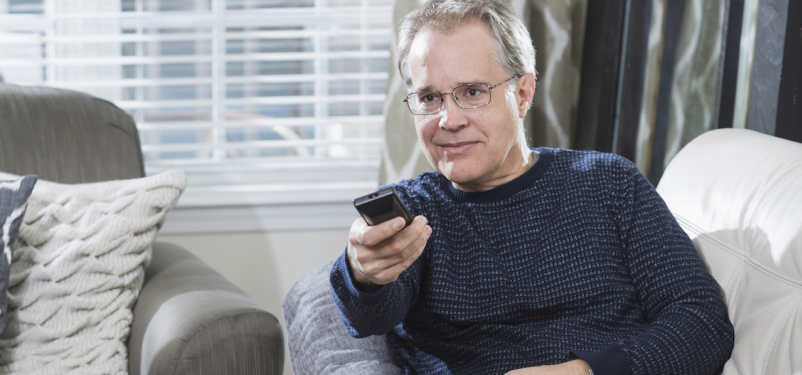 Mature man watching TV in living room