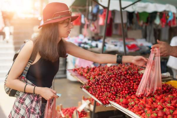 Buying fruit at outdoor market.