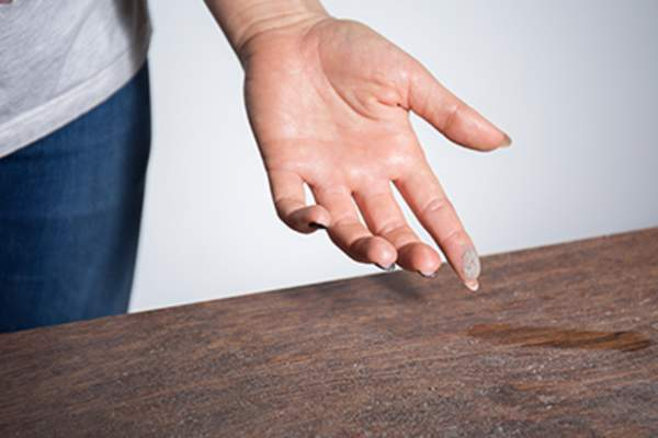 Dust on woman's finger that she wiped from a dusty table.