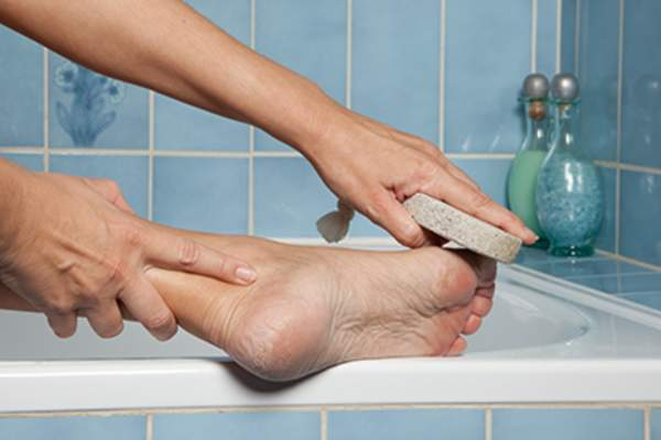 Woman using pumice stone on foot in bath.