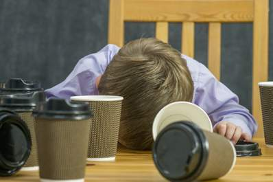 Boy asleep at the table with coffee cups around.