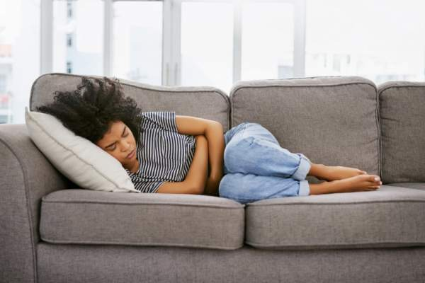 Young woman on couch having stomach pain