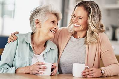 Senior woman drinking coffee with her caregiver.