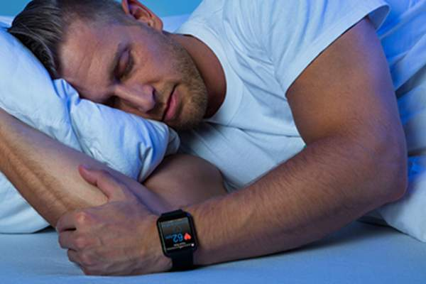 Man sleeping with a sleep tracking device.