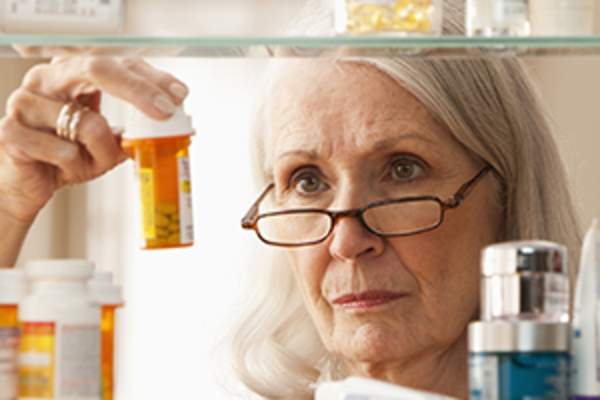 Women with medication in medicine cabinet image.