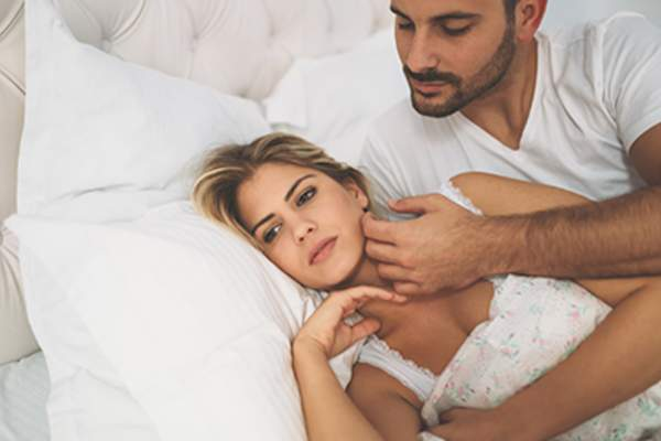 Woman unhappy with man while cuddling in bed.