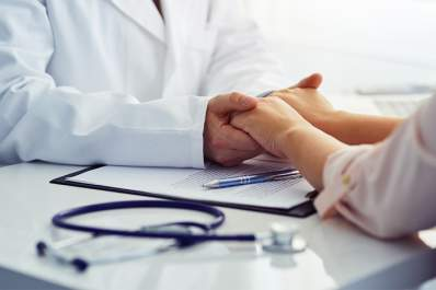 Doctor holding hands with patient in support.