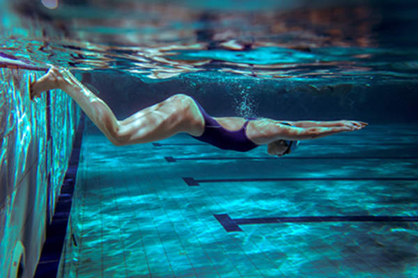 Woman swimming to improve back pain and sleep.