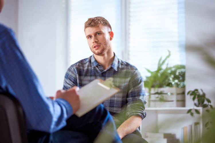 young man talking to therapist