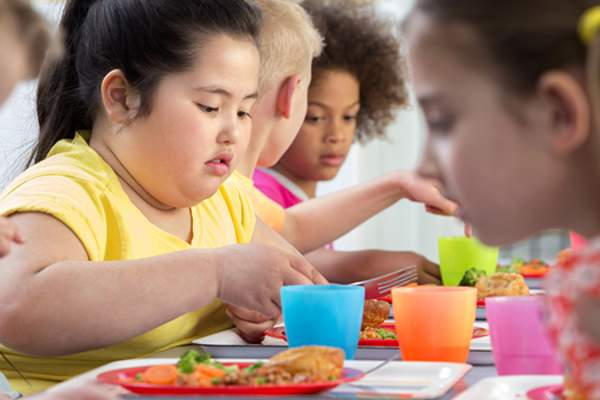 Overweight child eating lunch at school.